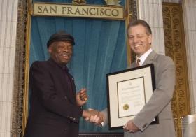 À cette occasion, Willie Brown, maire de San Francisco (à gauche) a présenté une proclamation à l'Église en saluant « ses efforts pour rendre la région de la baie un endroit meilleur pour tous, quels que soient leur origine, leur couleur, leurs croyances et leur milieu.»